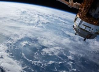 Earth from space with satellite in foreground